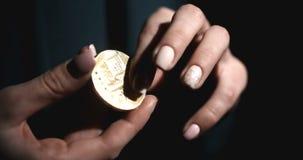 Kobieta rzuca monetą Kobieta trzymająca w ręku monetę bitmonową Ciemny na tle zbiory wideo