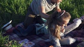 Mooie jonge man in het park met zijn kleine kinderen die plezier hebben Spelen met meisjes Ze liggen op het gras, lachen, hun stock footage