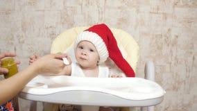 Le bébé mange de la purée de pommes de terre dans un chapeau rouge du Père NoÃ«l. Maman nourrit la petite bouillie du père No clips vidéos