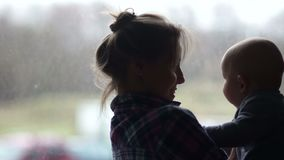 Baby en zijn moeder kijken elkaar aan en lachen Twee silhouetten tegenover het raam Moederdag, Kinderdag stock video
