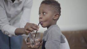 爱心母亲帮助非洲小男孩用管子喝玻璃水 母子关系 快乐 影视素材