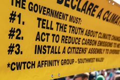 London, UK - April 15, 2019: Extinction Rebellion campaigners yellow banner of three core demands for the government of United