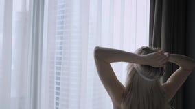 酒店客房的早晨 年轻女性坐在舒适的床上,戴着面具睡在头上 摩天大楼的窗户 股票视频