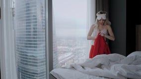 酒店客房的早晨 年轻女性坐在舒适的床上,戴着面具睡在头上 摩天大楼的窗户 影视素材