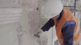 橙色成套装备命中的修造的工作者与白色墙壁的锤子零件 股票录像