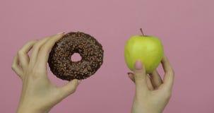 Tenue des mains de beignets et de pommes Choix de beigne contre pomme Aliments sains ou en jonque banque de vidéos