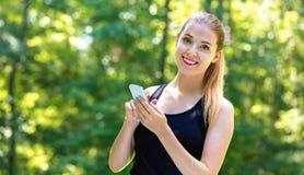 使用她的电话的年轻女人 库存照片