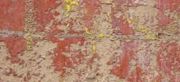被绘涂灰泥的老破裂被风化的破旧红色黄色剥了墙壁横幅背景 免版税库存照片