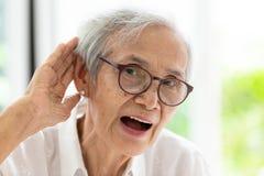 Mulher superior asiática que escuta por hand's até a orelha, tendo a dificuldade na audição, mulher idosa duramente a ouvir-se, fotos de stock