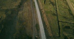 Коптер летает над красивой сельской местностью на поле Автомобили, направляющиеся по дорожной дороге вблизи моря видеоматериал