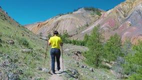 El inclinarse que camina turístico de la mujer en emigrar polos Visiónes desde una altura del valle con las montañas anaranjadas  metrajes