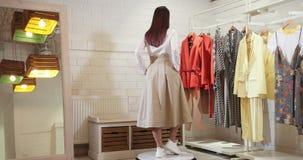 Una Bella Ragazza Gira Intorno All'Asse Sul Tappeto Mostra Il Modello Dell'Abbigliamento Un Modello In Camicia Bianca E Beige stock footage