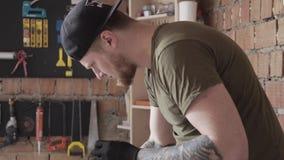 Professionele timmerman in kap werkend met elektrische draden Tot veel gereedschappen voor meubelfabricage Begrip hand stock videobeelden