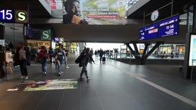 Berlin, Tyskland, den 8 maj 2019: Passagerare på tågstation Grupp av personer med bagage som går på upptagen flygplatsterminal Cr lager videofilmer