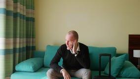 Pan shot de um empresário confiante e alegre falando de celular Um jovem empresário pede táxi por telefone Ele senta-se vídeos de arquivo