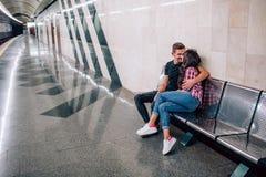 E r De mooie jonge man en de vrouw zitten samen Hij omhelst haar en kus stock afbeelding