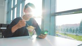 Luchthaven die wachten op een vlucht per vliegtuig Tien meisje eet salade en ziet er smartphone uit Internet in een café luchthav stock footage