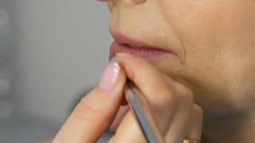Mulher adulta de meia idade num salão de beleza A lista de estilos compõe lábios mestres com batom usando pincel especial Desvane filme