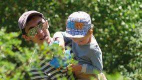 Vater mit seinem Sohn in seinen Armen gehen im Freien Papa und Sohn im Gebirge glücklicher Vater spielt mit seinem Sohn stock footage
