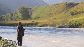 Vissers vangen vis tegen de achtergrond van een berglandschap Vissers toeristenroosters in een bergrivier Hobby stock video