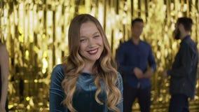 Portret młodej atrakcyjnej dziewczyny na złotym tle dziewczyna w inteligentnej zielonej sukience na imprezie 4K zbiory wideo