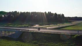 Homem em motocicleta passa por um pôr do sol na junção Foto de dron de rastreamento aéreo 4K filme