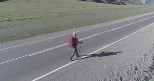 在柏油路上搭便车游客的飞行 夏日大型农村山谷 背包远足男 影视素材