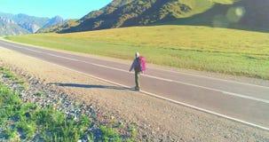 在柏油路上搭便车游客的飞行 夏日大型农村山谷 背包远足男 股票录像