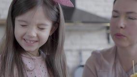 Portrait eines kleinen lustigen Mädchens, das ihrer Großmutter beim Kochen von Nudeln hilft Das Kind bricht lange Nudeln und läch stock video footage