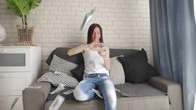 En glad leende ung flicka sitter på soffan och kastar upp dollar Begreppet lycka och vinst, motivation långsam arkivfilmer