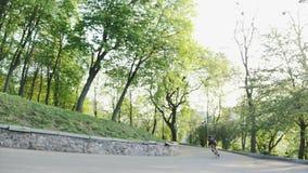 Profi-Motorradfahrer, der auf der kurvigen Straße mit schwarzer Jersey und kurzen Hosen steht Radfahrer, der den Hügel hinunterfä stock video