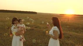 Mutter blühende Seifenblasen glückliche Kinder lächeln Töchter freuen sich und lächeln, Blasen fliegen bei Sonnenuntergang im Par stock video footage