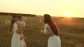 Mutter blühende Seifenblasen glückliche Kinder lächeln Töchter freuen sich und lächeln, Blasen fliegen bei Sonnenuntergang im Par stock footage