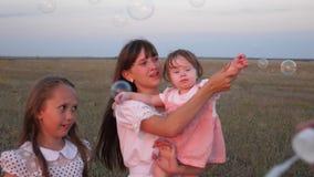 Mamá feliz jugando con niños haciendo burbujas de jabón los niños atrapan burbujas y ríen en el parque en verano Lento almacen de video