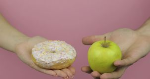 Tenue des mains de beignets et de pommes Choix de beigne contre pomme Aliments sains ou en jonque clips vidéos