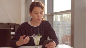 Luchthaven die wachten op een vlucht per vliegtuig Tien meisje eet salade en ziet er smartphone uit Internet in een café lifestyl stock footage