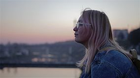 Mooie rode zonsondergang over de rivier Het meisje zit op het water en kijkt in de verte Schitterend cinematografisch frame stock footage