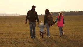 家人带着狗在平原旅行 紧密家庭的团队协作 母亲、小孩和女儿和宠物 影视素材