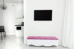 在现代轻的样式的公寓内部 在墙壁和一条长凳上的电视与颜色口音 免版税库存图片