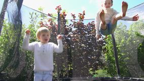 跳跃在绷床的男孩和女孩在房子后院 慢动作射击 影视素材
