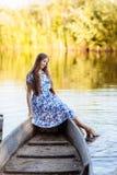 坐在汽艇的年轻美女生活方式画象 女孩获得乐趣在水的小船 库存图片