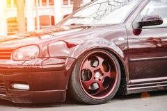 在街道上停留的一辆低调整的姿态汽车的习惯棕色伪造的轮子 空气停止的肮脏的驾驶低底盘汽车兜风者在好日子 免版税库存图片