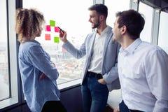 小组年轻企业家在工作过程中寻找企业解答在办公室 商人会议 图库摄影