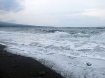 击中巴厘岛的含沙黑火山的沙滩波浪、海浪和海泡沫 在Amed,海是安静,但是在附近的波浪 图库摄影