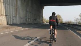 年轻适合的骑自行车者骑马自行车在桥梁下 种族的循环的训练 头戴黑成套装备和盔甲的男性骑自行车者 影视素材