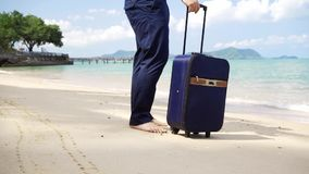 Zakenman loopt langs de kust van een mooie zee met een koffer mannelijke vrolijke vakantie freelance concept, lang stock videobeelden