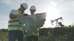 谈论队的工程师油泵领域的维护 工作在炼油厂的工程学队 两名工作者 影视素材