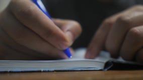 El hombre escribe en cuaderno escritura de la mano del hombre en una libreta de la forma de vida educación del negocio del concep metrajes