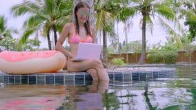 坐与膝上型计算机的年轻女性自由职业者在水池附近 繁忙在假日期间 遥远的工作的概念 影视素材
