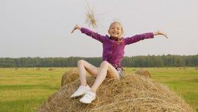 驱散在乡下领域的无忧无虑的少年女孩干燥秸杆 愉快的女孩少年坐干草堆 ?? 股票视频